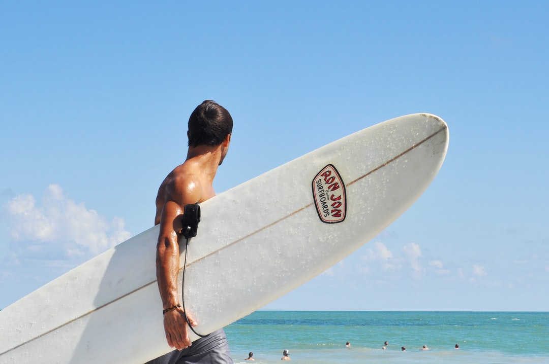 A man carrying a surf board in the ocean
